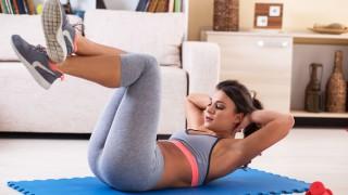 Eine junge Frau trainiert zuhause