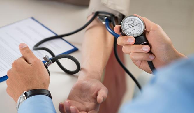 Ein Arzt misst den Blutdruck am Arm eines Patienten