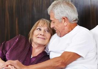 Ein älteres Ehepaar blickt sich im Bett verliebt an