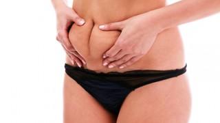 Eine leicht übergewichtige Frau begutachtet ihr Bauchfett