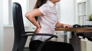 Eine Frau am Schreibtische hat Rückenschmerzen