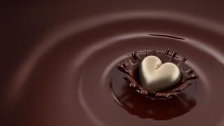 Ein goldenes Pralinenherz fällt in flüssige Schokolade