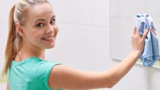 Eine junge Frau wischt ihren Badezimmerspiegel