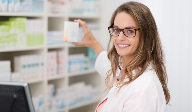 Eine junge Apothekerin greift nach einem Medikament