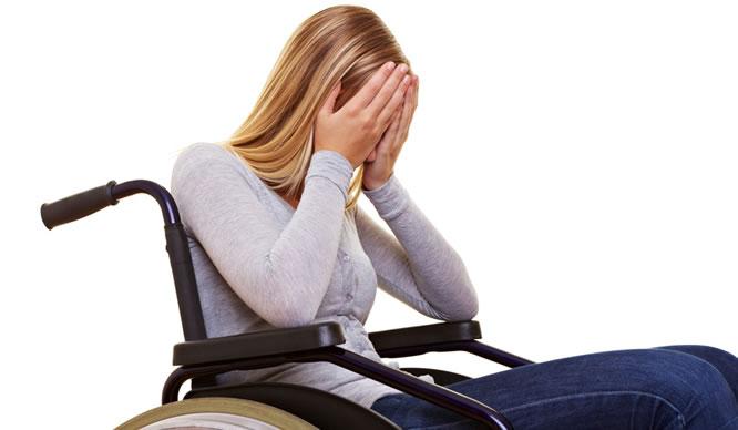 Eine junge, blonde Frau sitzt im Rollstuhl