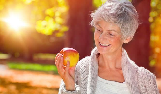 Eine ältere Frau hält einen Apfel in der Hand