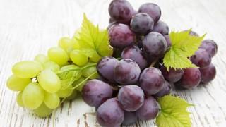 Grüne und rote Weintrauben auf einem Holzbrett