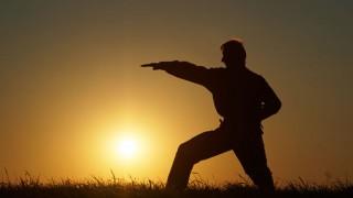 Ein Mann macht im Sonnenuntergang Kung Fu-Übungen