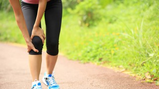 Eine junge Sportlerin erleidet einen Wadenkrampf
