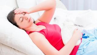 Eine junge Frau liegt mit Wärmflasche im Bett