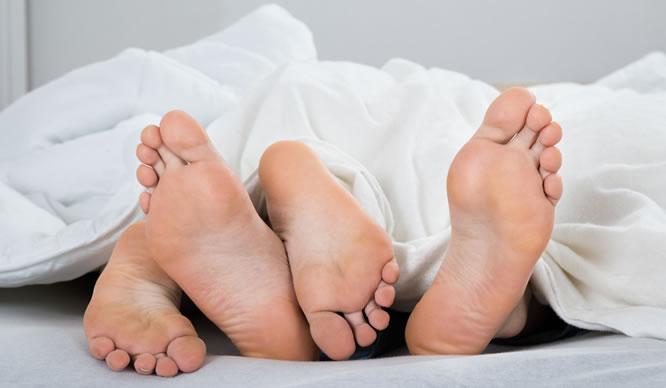 Die Füße eines Pärchens beim Liebesspiel