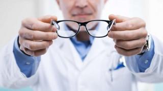Ein Augenarzt reicht seinem Patienten eine Brille