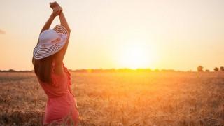 Eine Frau genießt den Sonnenuntergang in einem Kornfeld