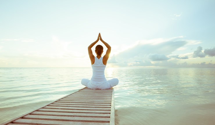 Eine Frau macht Yoga-Übungen auf einem Bootssteg