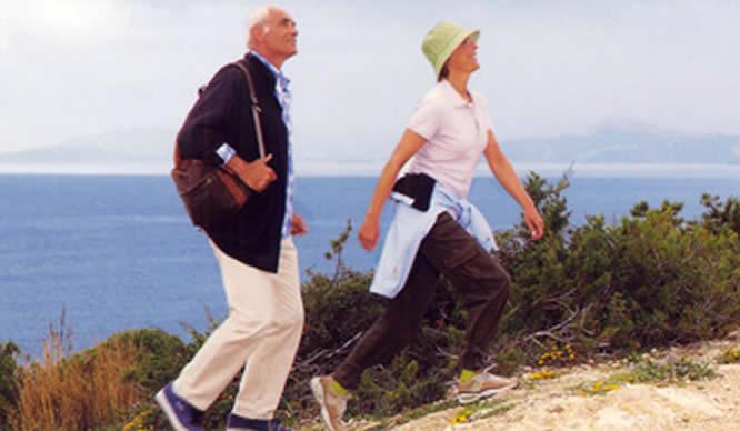 Eine älteres Ehepaar spaziert am Meer