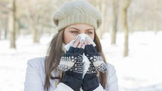 Eine junge Frau putzt ihre Nase