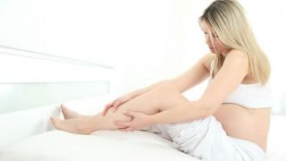 Eine Schwangere erleidet im Bett einen Wadenkrampf