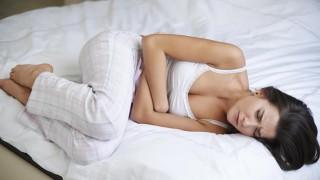 Eine junge Frau hält sich bei Verstopfung den Bauch