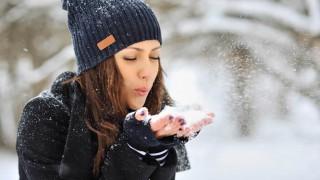 Eine Frau bläst Pulverschnee aus beiden Händen