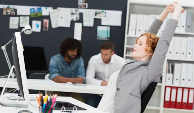 Eine Frau streckt sich am Arbeitsplatz