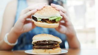 Eine Frau isst zwei Burger