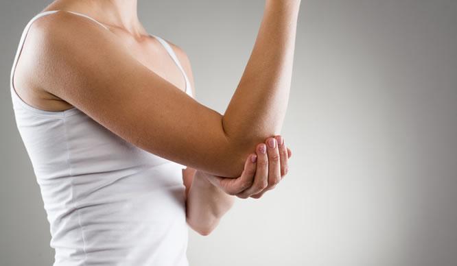 Eine Frau hat Muskelschmerzen am Arm