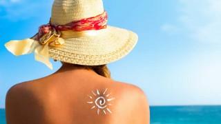 Eine junge Frau sitzt am Strand in der Sonne