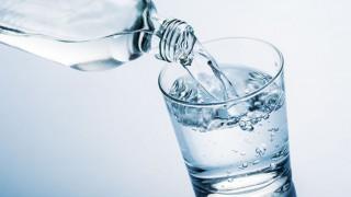 Wasser wird aus einer Flasche in ein Glas gegossen