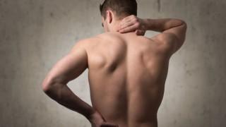 Ein Mann mit Muskelkater massiert sich den Nacken