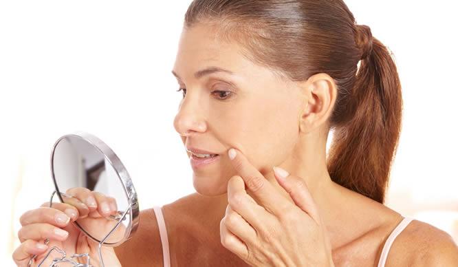 Eine Frau pflegt vor dem Spiegel ihre Haut