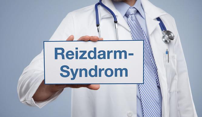 Ein Arzt hält ein Schild mit der Aufschrift Reizdarm Syndrom