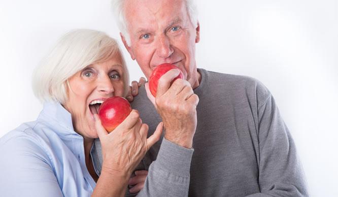 Zwei ältere Eheleute beißen in Äpfel