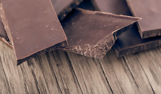 Dunkle Schokoladenstücke auf einem Holzbrett