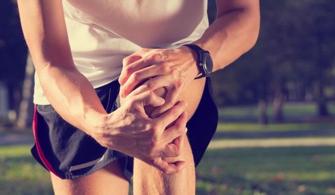 Ein Läufer hält sich das linke Knie