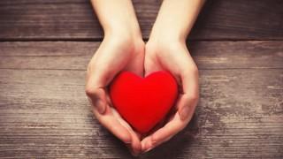 Zwei Hände halten ein rotes Herz