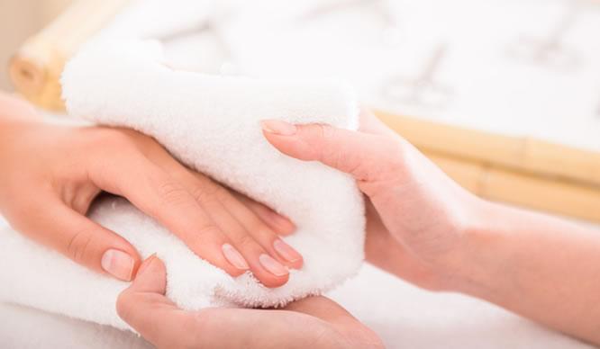 Hand mit natürlichen Nägeln bei der Pflege