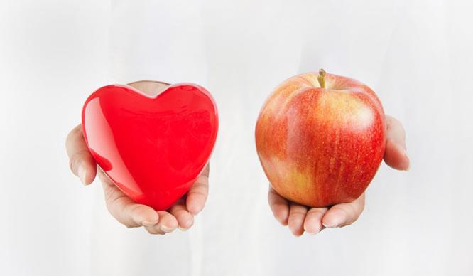 Eine Ärztin hält einen Apfel und ein Herz aus Plastik
