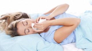 Eine Frau im Bett leidet an Hausstaub-Allergie