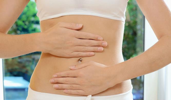 Eine Frau drückt beide Hände auf ihren Darm
