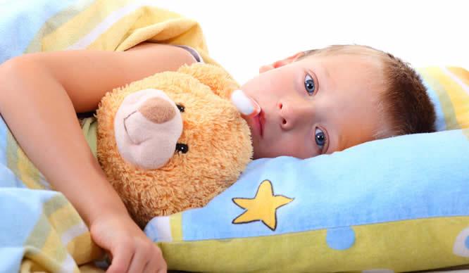 Ein kleiner Junge liegt mit Fieber im Bett