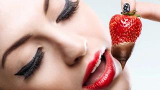 Eine Frau isst eine Erbeere mit Schokosoße