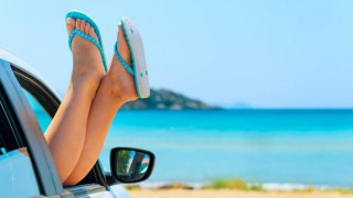 Eine Frau streckt ihre Füße entspannt aus dem Autofenster
