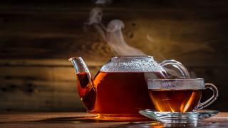 Eine dampfende Teekanne mit einer Tasse