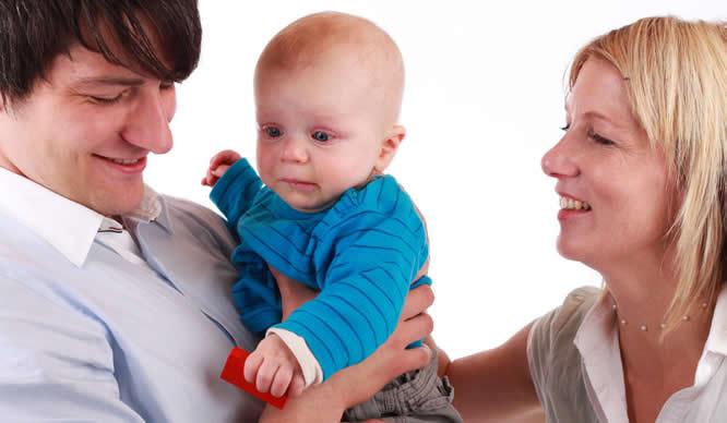 Ein fremdelndes Baby auf dem Arm seiner Eltern