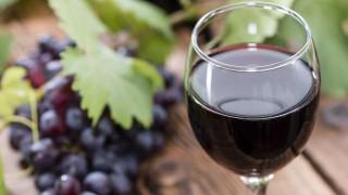 Ein Glas Rotwein mit Trauben