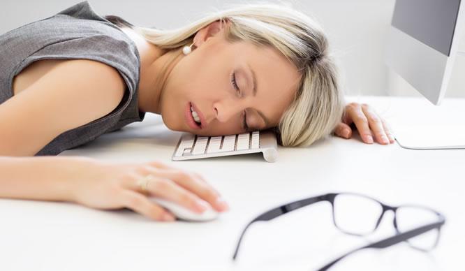 Eine Frau schläft am Arbeitsplatz