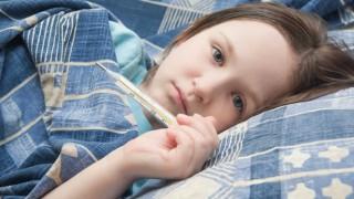 Eine kleines Mädchen liegt mit Fieber im Bett