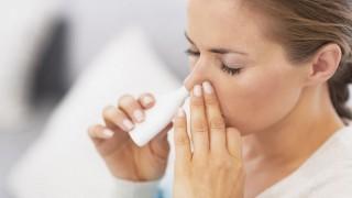 Eine junge Frau verabreicht sich Meerwasser-Nasenspray