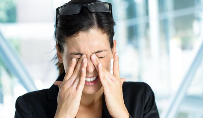 Eine junge Frau reibt ihre entzündeten Augen