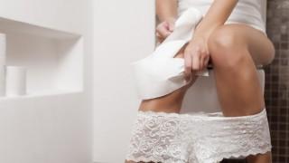 Eine junge Frau sitzt auf der Toilette